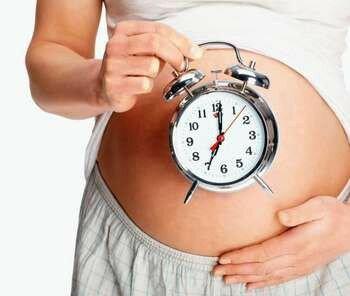 Часы на фоне беременной девушки