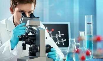 Мужчина смотрит в микроскоп