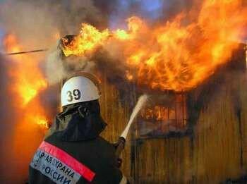 Пожарный тушит здание