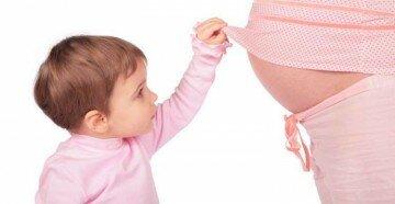 Ребенок заглядывает на живот беременной мамы