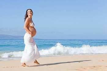 Беременная идет по пляжу