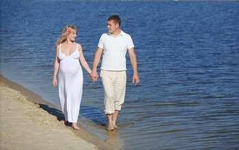 Беременная с мужчиной прогуливаются по пляжу