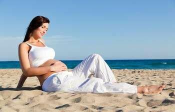 Беременная сидит на пляже