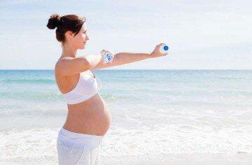 Беременная занимается гимнастикой на море