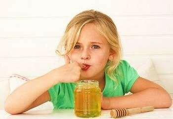 Девочка облизывает палец от меда