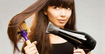 Девушка выпрямляет волос феном