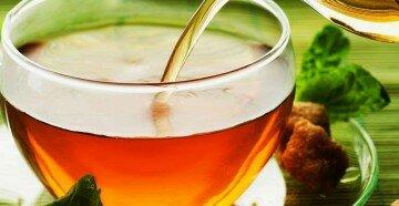 Из прозрачного чайника льётся чай в прозрачную чашку