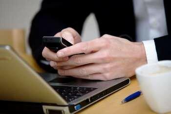 Мужчина держит телефон у ноутбука